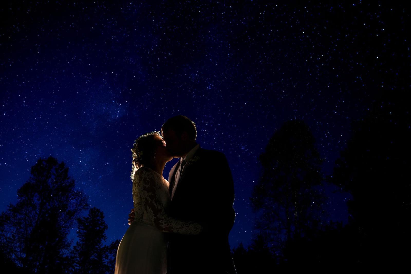 Bride and groom kissing under the stars at Atlanta wedding