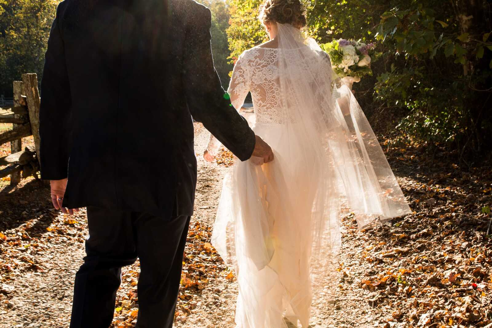 Bride and groom walking down dust road into sunset