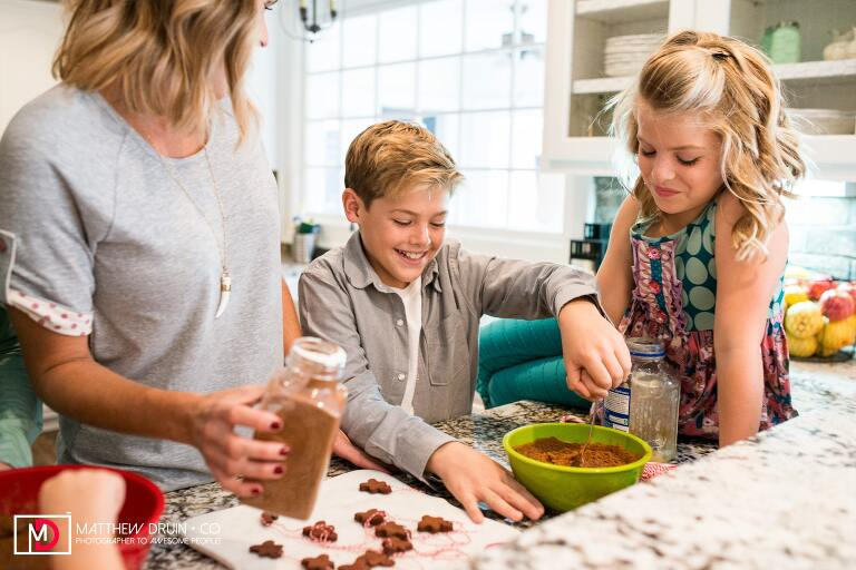 Kids stirring cinnamon applesauce ornament batter with mom in kitchen for winter family holiday traditions for Little Black Dress magazine