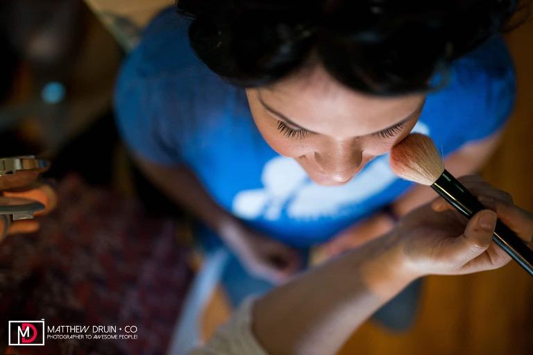 Bride getting makeup for wedding wearing blue shirt