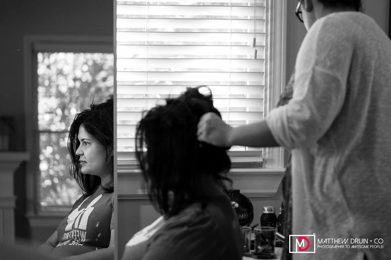 Reflection of bride in mirror getting hair done for wedding in black and white