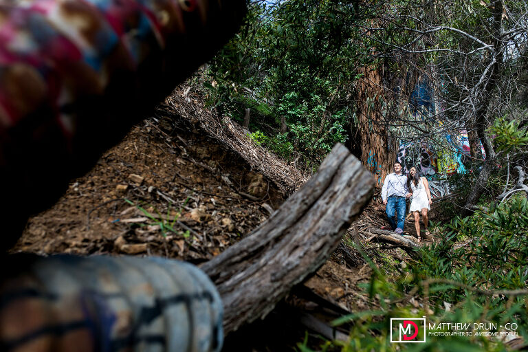 Couple walking through woods at Murphy's Ranch at Los Angeles Engagement Session
