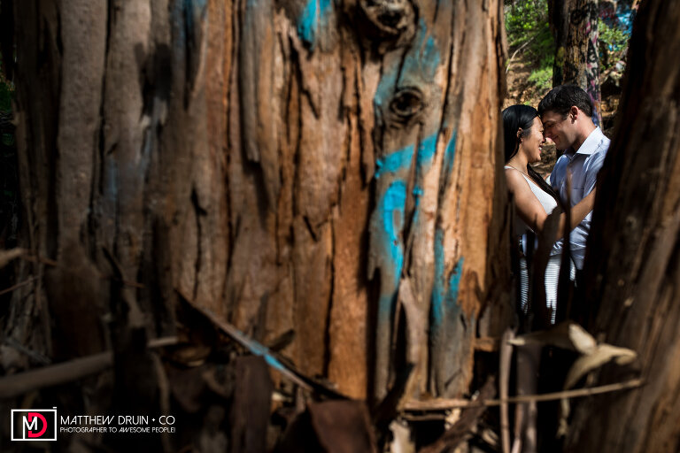 Couple kissing through graffiti trees at Murphy's Ranch at Los Angeles Engagement Session