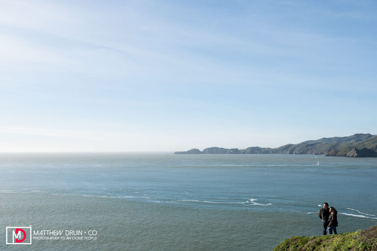 Couple standing on cliff by ocean during their San Francisco Golden Gate Bridge engagement