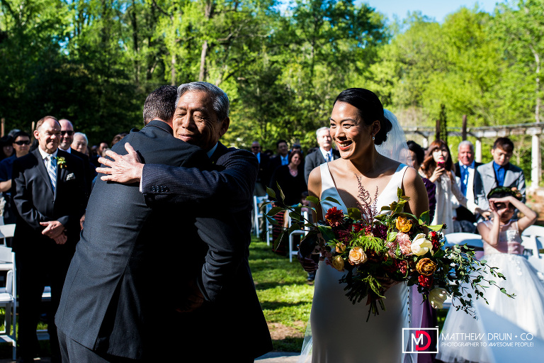 Father of bride hugging groom during wedding ceremony at Chinese Inspired Fusion Wedding At Cator Woolford Gardens