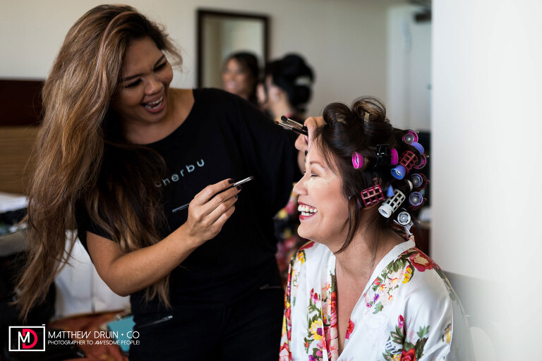 Bride laughing with makeup artist at Honolulu Hawaii Wedding