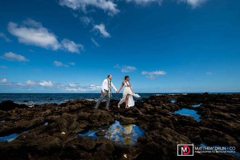 Bride and groom running across volcanic black rocks by ocean with reflection in puddle Honolulu Hawaii