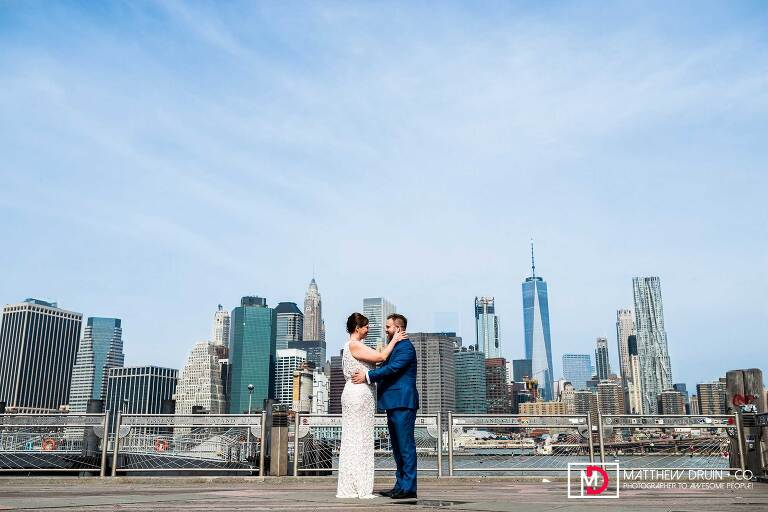 Bride and groom looking at each other at first look by east river with New York City skyline
