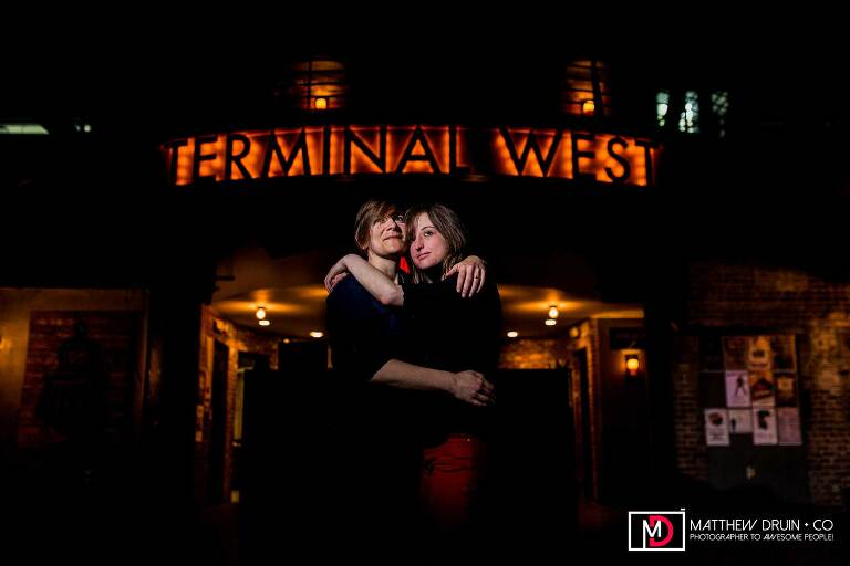 Engaged gay couple holding each other in front of Terminal West sign