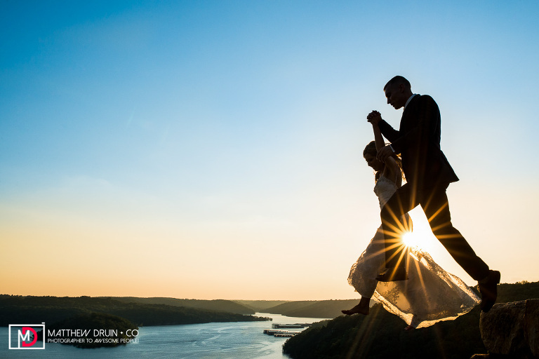 Bride and groom jumping off mountain cliff over lake at sunset at Big Cedar Lodge Branson Missouri wedding