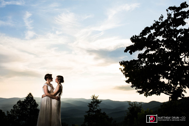 Bride and bride standing on cliff during sunset with mountain landscape in background at Amicalola Falls lgbt wedding reception