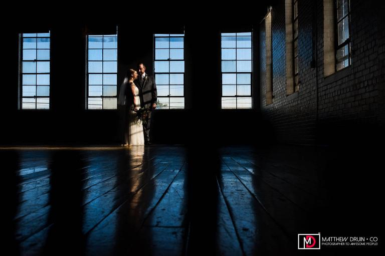 Bride and groom standing in sunset light filtering through warehouse window at Atlanta Ambient Plus Studio wedding