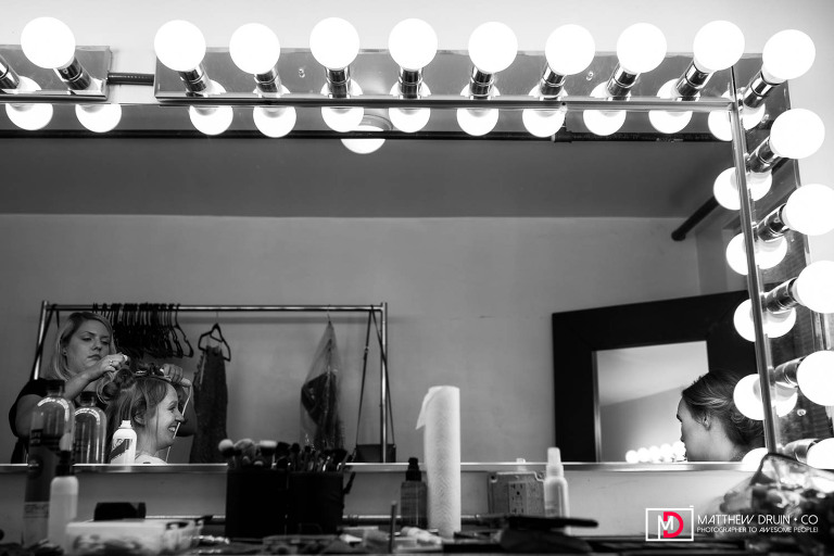 Reflection of bride and bridesmaid in mirror while getting ready for Atlanta Ambient Plus Studio wedding