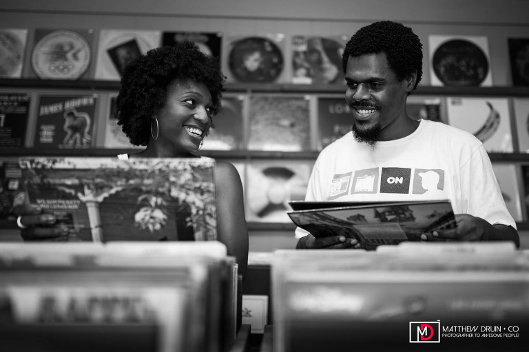 Engaged couple laughing while looking through record albums at record store engagement session in Atlanta, Georgia