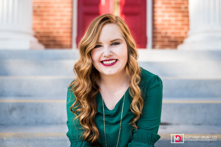 Sequoyah High School Senior wearing green dress sitting on stairs looking at camera in downtown Canton
