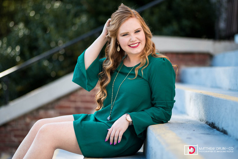 Sequoyah High School Senior wearing green dress and touching hair while sitting on stairs looking at camera in downtown Canton