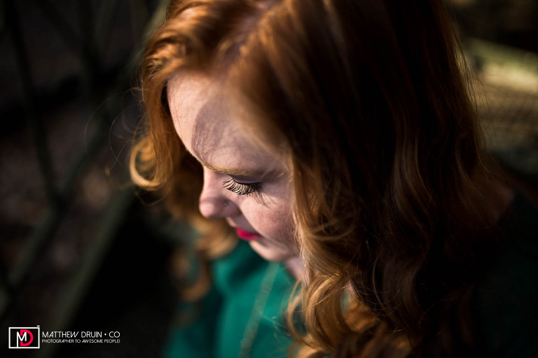 Sequoyah High School Senior wearing green dress looking down with golden sunlight hitting face in downtown Canton