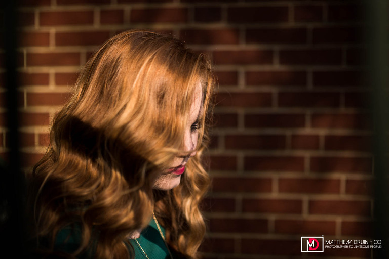 Sequoyah High School Senior with red hair looking down with golden sunlight hitting face in downtown Canton