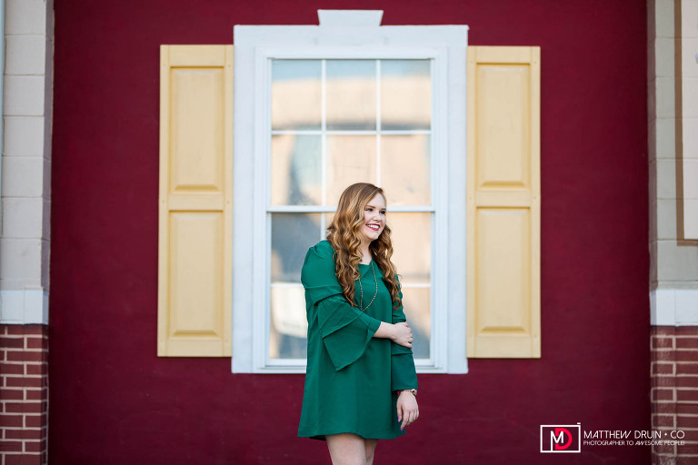 Sequoyah High School Senior wearing green dress  framed with in window frame against red and yellow wall in downtown Canton