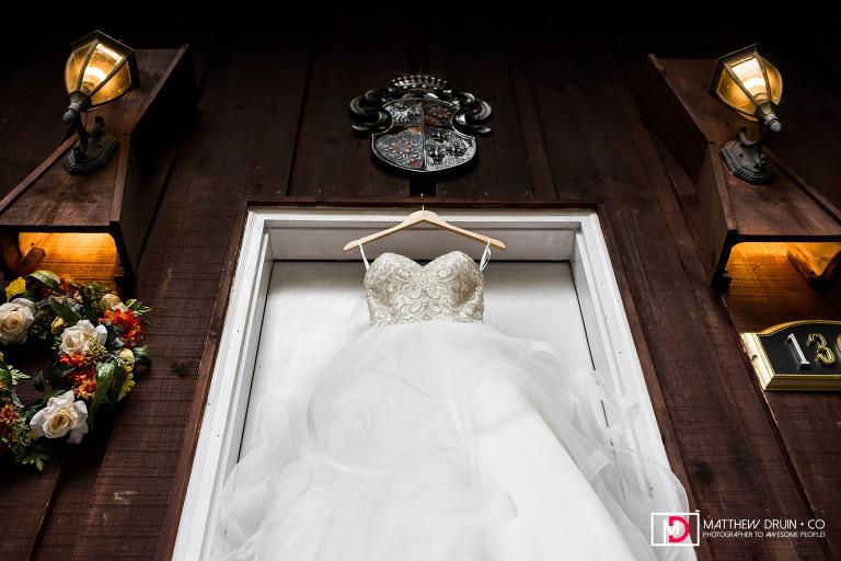 Brides wedding dress hanging on cabin door before Neverland Farms wedding