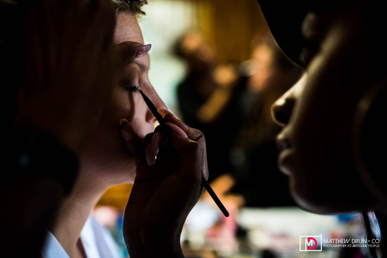 Bride getting eyeshadow applied by makeup artist before Neverland Farms wedding