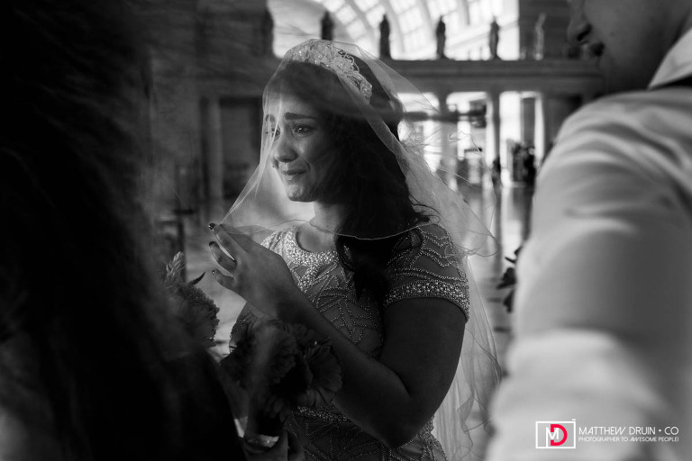 Black and white photo of bride under veil crying before Grand Central Station Washington DC wedding ceremony