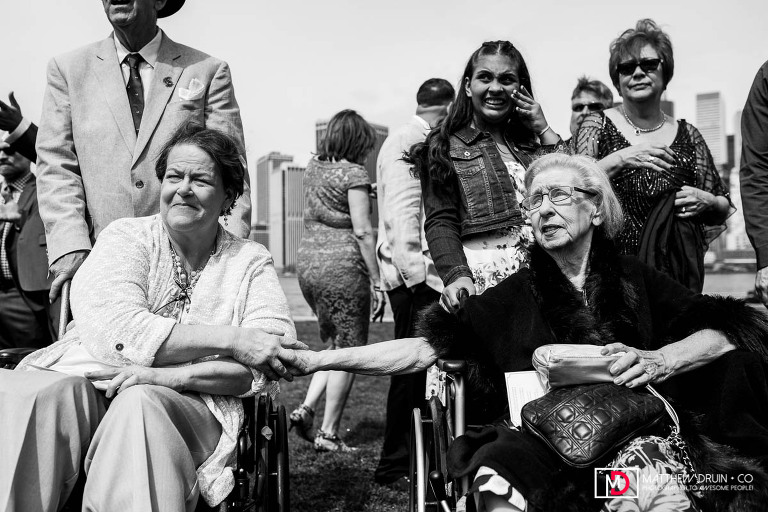 Grandparents in wheel chairs reaching and holding hands at New York City park wedding ceremony