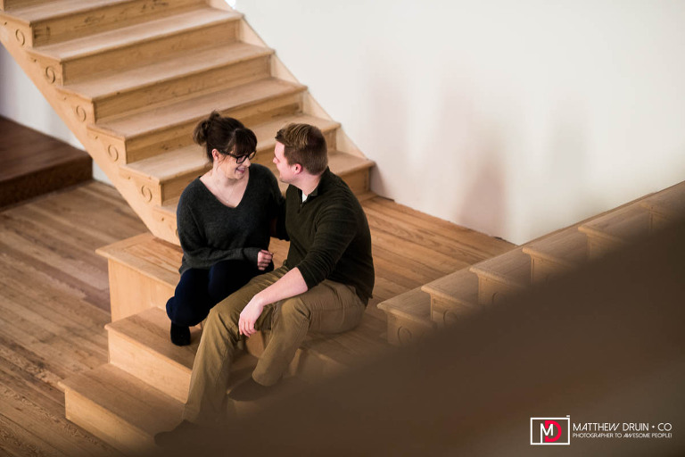 Couple hugging on stairs in their converted church house during Michigan engagement session