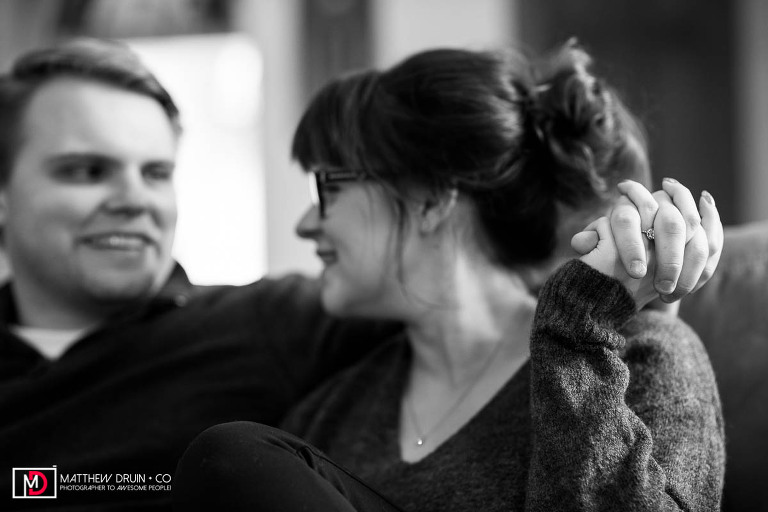 Couple hanging out on couch in their converted church house showing off engagement ring during Michigan engagement session