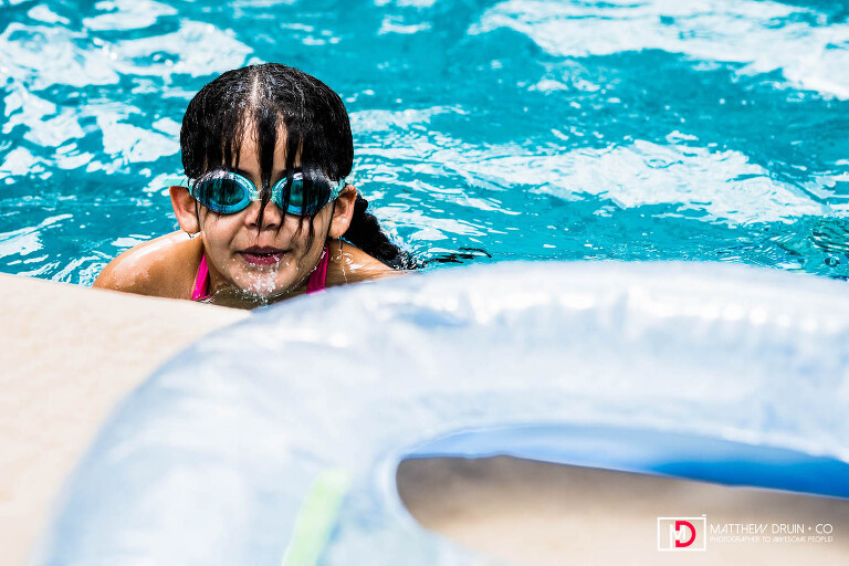 Girl in swimming pool wearing goggles looking over edge with water running down her face at Atlanta birthday party