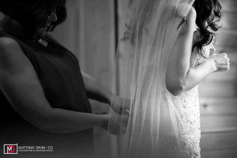 Bridesmaids helping bride get into wedding dress in Tennessee mountain cabin for elopement Gatlinburg wedding