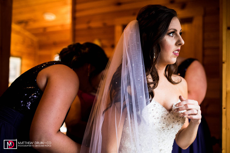 Bride looking out window while bridesmaids help her get into wedding dress in Tennessee mountain cabin for elopement Gatlinburg wedding
