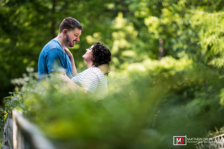 Engaged couple hugging and about to kiss at Athens botanical gardens engagement session