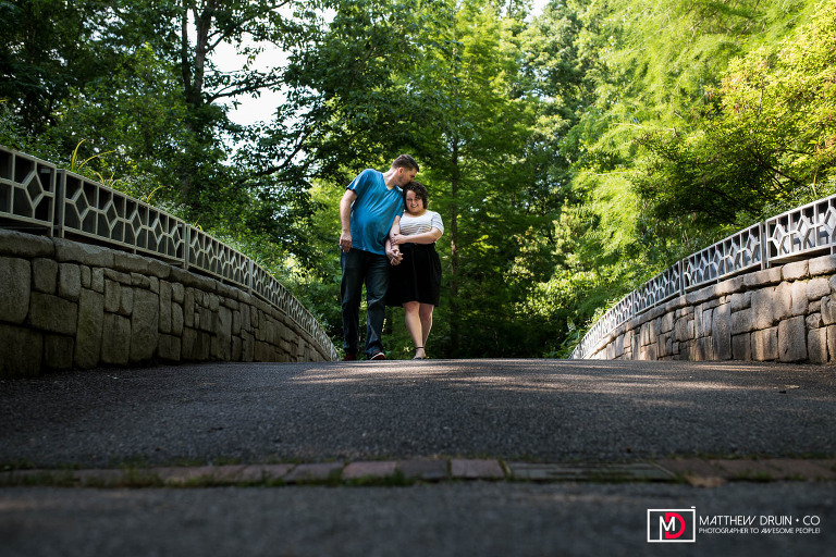Guy kissing girl on head while walking and holding hands across bridge at Athens botanical gardens engagement session