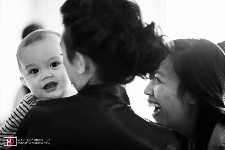 Bride laughing at baby and bridesmaid while getting ready for San Francisco wedding