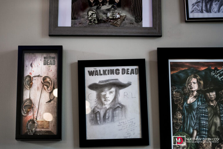 Human ears necklace and Carl artwork hanging on wall of Walking Dead house of getting ready Atlanta festival wedding location.