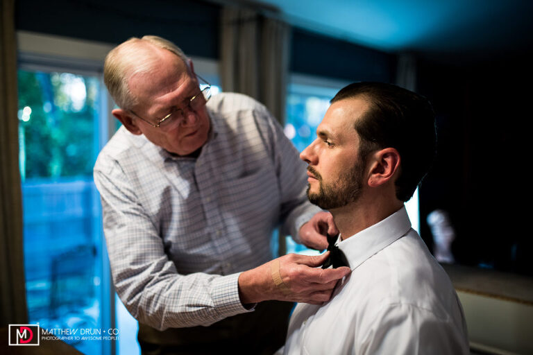 Dad helping groom put on bowtie for intimate Atlanta wedding at Rays At Killer Creek