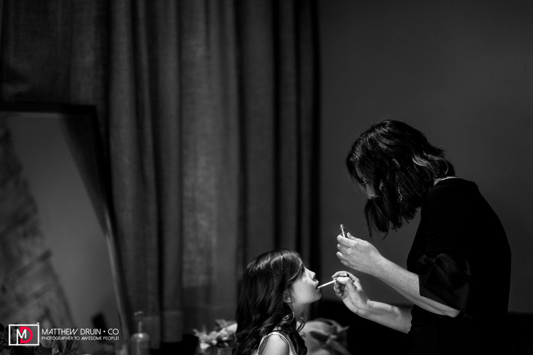 Mom puts lipstick on daughter while getting ready for intimate Rays At Killer Creek wedding