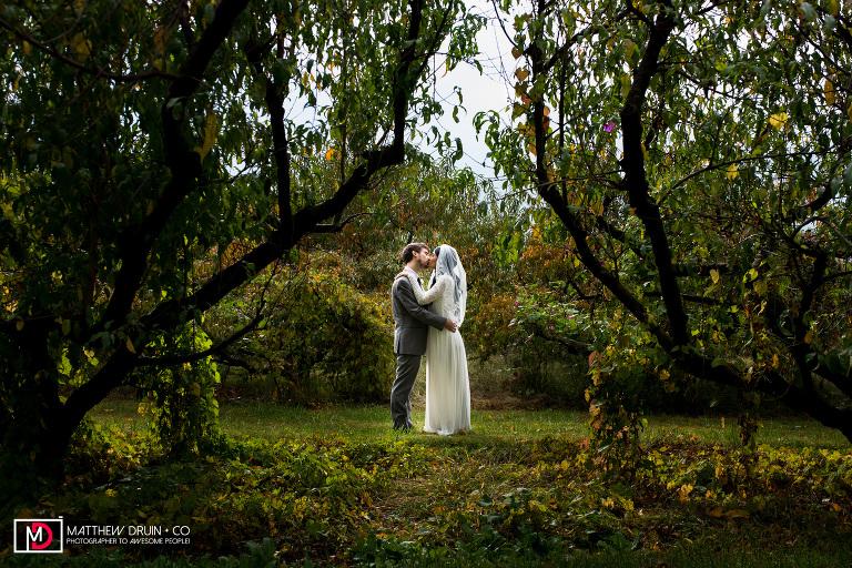 Bride and Groom kissing between two vineyard trees at sunset Atlanta wedding