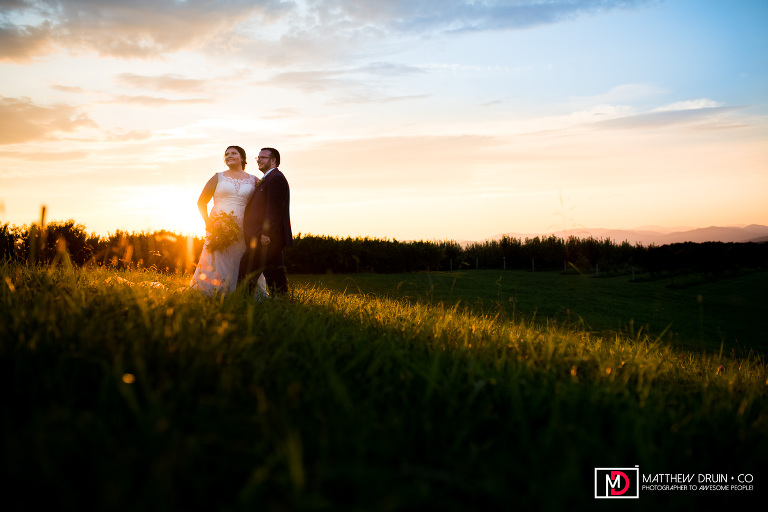 Bride and groom in vineyard field at sunset during South Carolina wedding